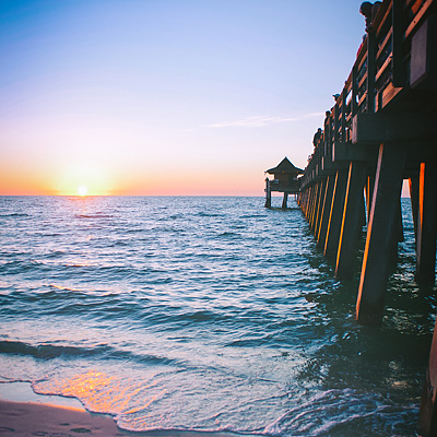 Photograph of the sun setting over the Gulf of Mexico with the Naples Pier.